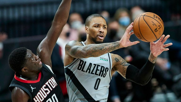 Portland Trail Blazers guard Damian Lillard, right, pass the ball away from Houston Rockets forward Khyri Thomas during the second half of an NBA basketball game in Portland, Ore., Monday, May 10, 2021.