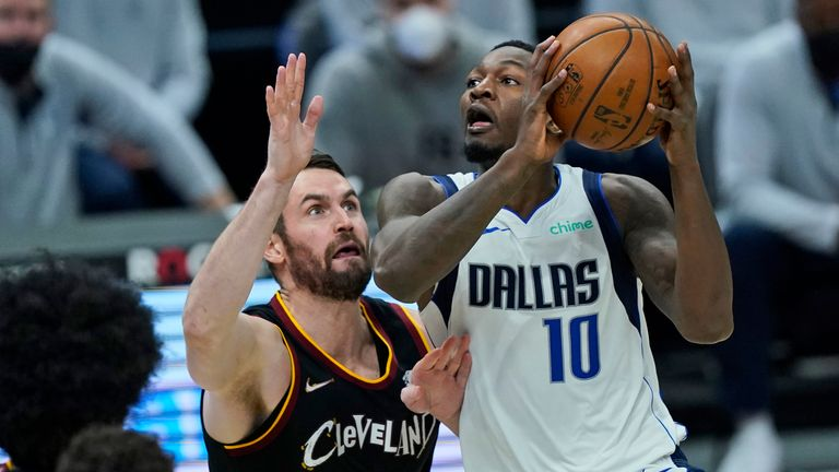 Dallas Mavericks' Dorian Finney-Smith (10) drives to the basket against Cleveland Cavaliers' Kevin Love (0) in the second half of an NBA basketball game, Sunday, May 9, 2021, in Cleveland. (AP Photo/Tony Dejak)