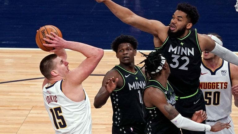 Denver Nuggets' Nikola Jokic (15) shoots as Minnesota Timberwolves' Karl-Anthony Towns (32) defends during the first half of an NBA basketball game Thursday, May 13, 2021, in Minneapolis.