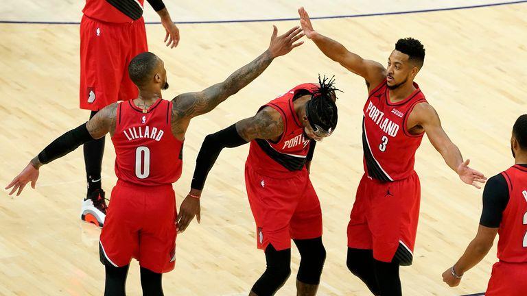 Portland Trail Blazers guard Damian Lillard high fives guard CJ McCollum over  forward Robert Covington during the second half of an NBA basketball game against the Phoenix Suns