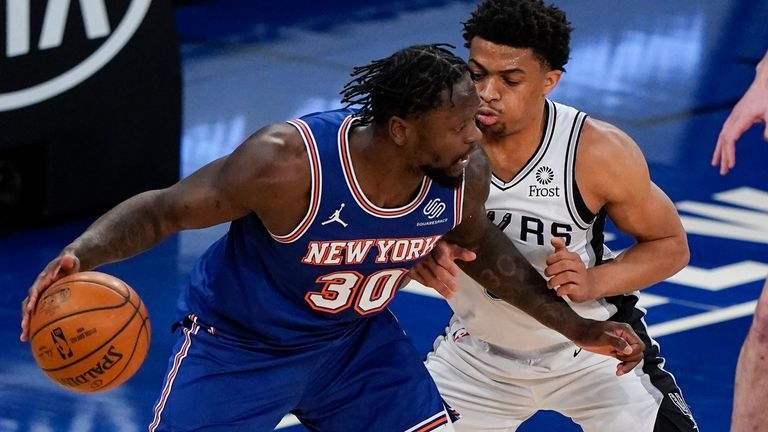 New York Knicks' Julius Randle (30) is defended by San Antonio Spurs' Keldon Johnson (3) during the first half of an NBA basketball game Thursday, May 13, 2021, in New York.