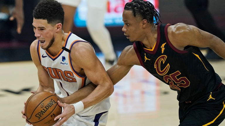 Phoenix Suns' Devin Booker, left, drives past Cleveland Cavaliers' Isaac Okoro in the first half of an NBA basketball game, Tuesday, May 4, 2021, in Cleveland.