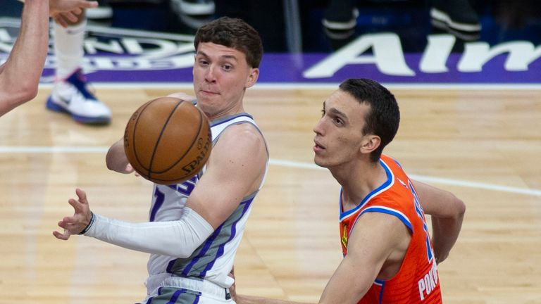 Sacramento Kings guard Kyle Guy (7) passes the ball as Oklahoma City Thunder forward Aleksej Pokusevski defends during the fourth quarter of an NBA basketball game in Sacramento, Calif., Sunday, May 9, 2021. (AP Photo/Hector Amezcua)