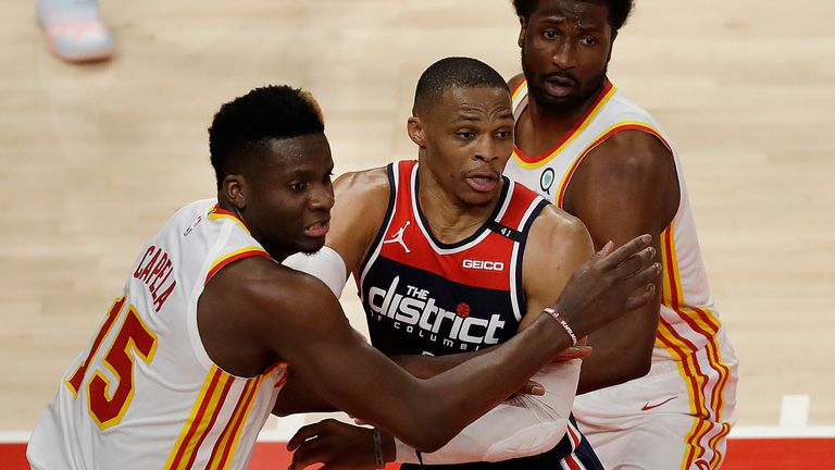 Atlanta Hawks' Clint Capela, left, guards Washington Wizards' Russell Westbrook in the second half of an NBA basketball game Monday, May 10, 2021, in Atlanta.