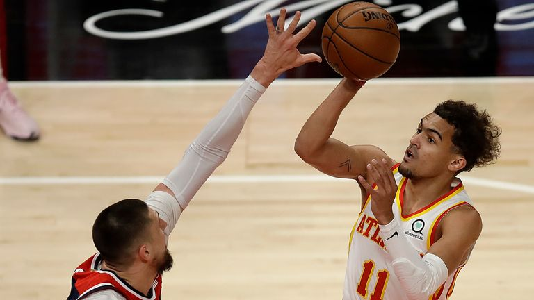 Atlanta Hawks' Trae Young, right, shoots over Washington Wizards' Alex Len during the first half of an NBA basketball game Monday, May 10, 2021, in Atlanta.