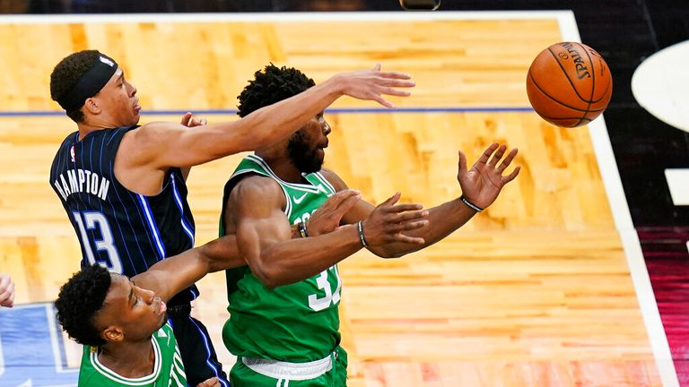 guard R.J. Hampton (13) tries to get a rebound against forward Aaron Nesmith, left, and forward Semi Ojeleye, right, during the first half of an NBA basketball game, Wednesday, May 5, 2021, in Orlando, Fla. (AP Photo/John Raoux)