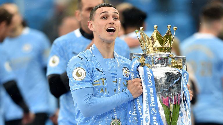 Phil Foden celebrates with the Premier League trophy