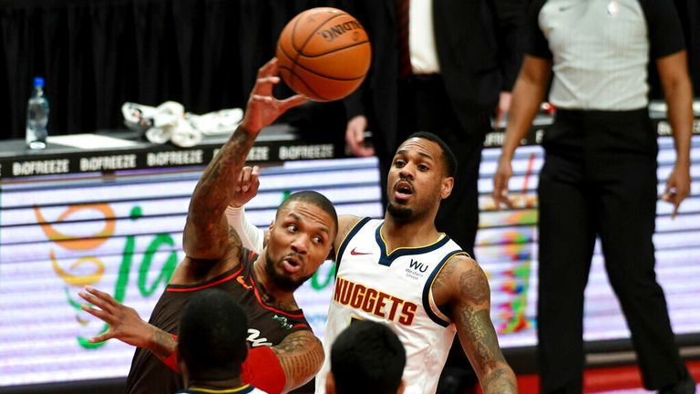 Portland Trail Blazers guard Damian Lillard, top, passes the ball on Denver Nuggets forward Paul Millsap, bottom, during the first half of an NBA basketball game in Portland, Ore., Sunday, May 16, 2021. (AP Photo/Steve Dykes)