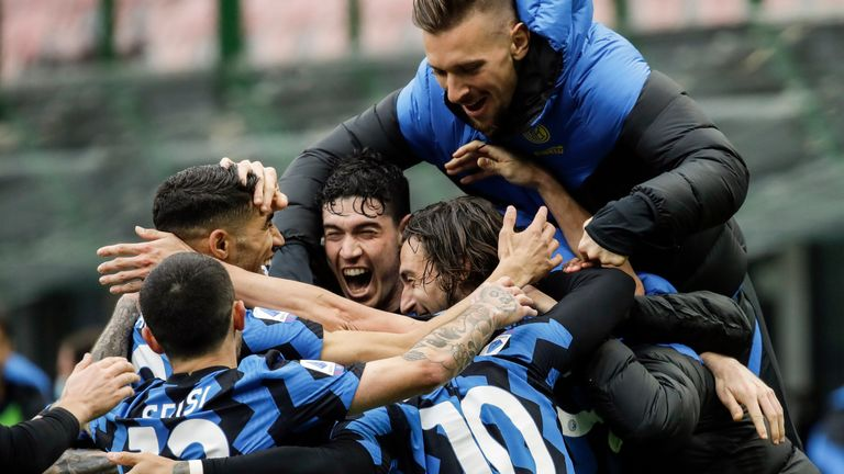 Inter Milan's Matteo Darmian, right, celebrates with teammates Alessandro Bastoni, Lautaro Martinez, Stefano Sensi and Achraf Hakimi, left, after scoring during a Serie A soccer match between Inter Milan and Cagliari at the San Siro stadium in Milan, Italy, Sunday, April 11, 2021. (AP Photo/Luca Bruno)