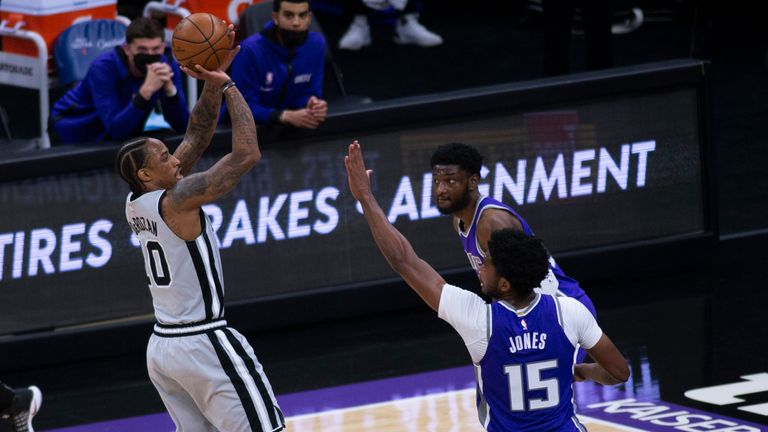 San Antonio Spurs forward DeMar DeRozan shoots the ball as he's defended by Sacramento Kings center Damian Jones