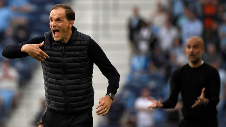 Chelsea's head coach Thomas Tuchel and Manchester City's head coach Pep Guardiola, background, gesture during the Champions League final soccer match between Manchester City and Chelsea at the Dragao Stadium in Porto, Portugal, Saturday, May 29, 2021.