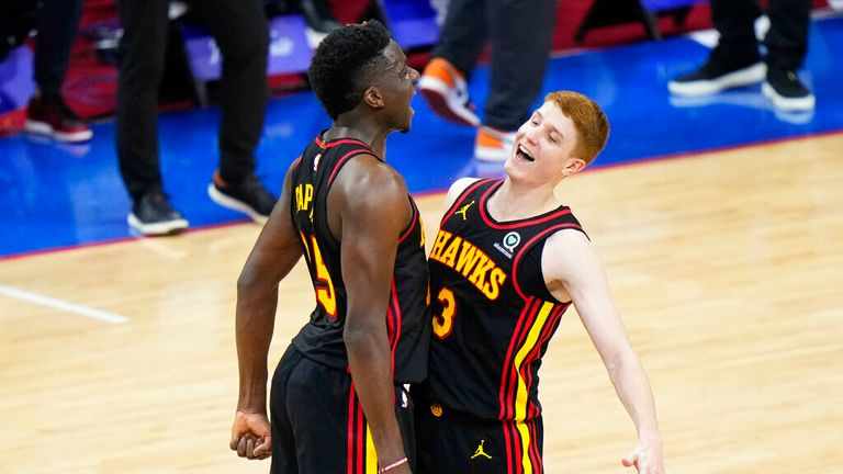 Atlanta Hawks' Kevin Huerter, right, and Clint Capela celebrate during the final seconds of Game 7 in a second-round NBA basketball playoff series against the Philadelphia 76ers, Sunday, June 20, 2021, in Philadelphia. (AP Photo/Matt Slocum)