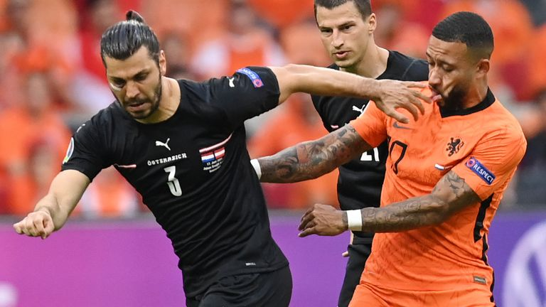 Austria's Aleksandar Dragovic, left, challenges for the ball with Memphis Depay of the Netherlands during the Euro 2020 soccer championship group C match between the The Netherlands and Austria at Johan Cruijff ArenA in Amsterdam, Netherlands, Thursday, June 17, 2021. (John Thys, Pool via AP)
