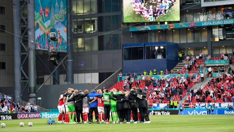 Denmark players gather together on the pitch as they return to resume the match