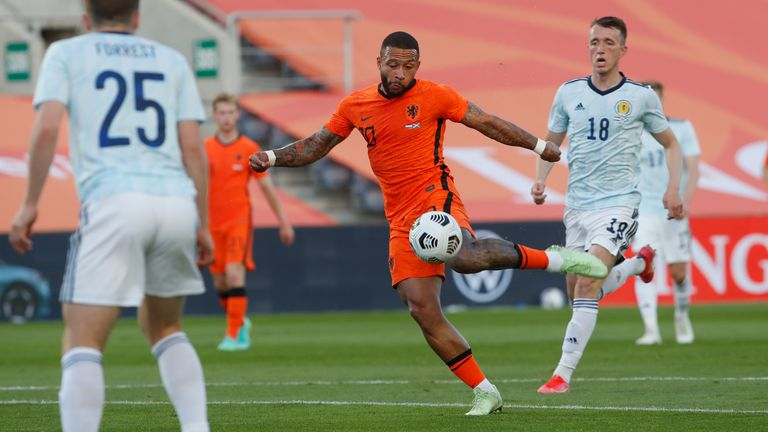 Netherlands' Memphis Depay, centre, scores his side's first goal during the international friendly soccer match between the Netherlands and Scotland at the Algarve stadium outside Faro, Portugal, Wednesday June 2, 2021. (AP Photo/Miguel Morenatti)