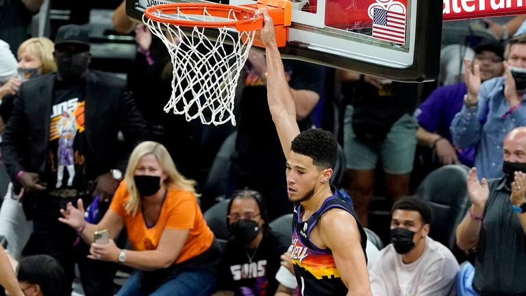 Phoenix Suns guard Devin Booker dunks against the Denver Nuggets during the first half of Game 2 of an NBA basketball second-round playoff series