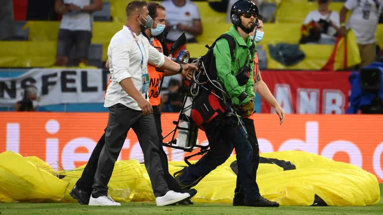 The paraglider was led off the pitch by security ahead of France and Germany's Euro 2020 clash (AP)