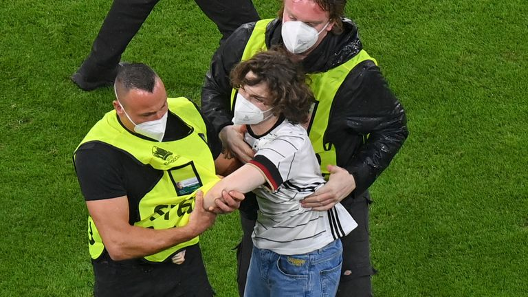 Stewards escort fan off the pitch at the Allianz Arena
