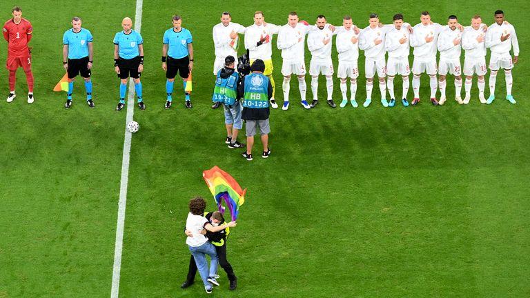 Los abanicos que agitan la bandera del arco iris son manejados por una criada