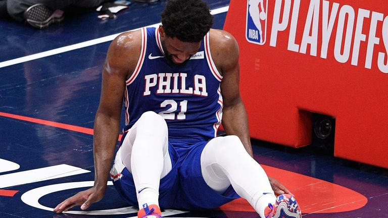 Joel Embiid grimaces in pain on the floor of the Capital One Arena
