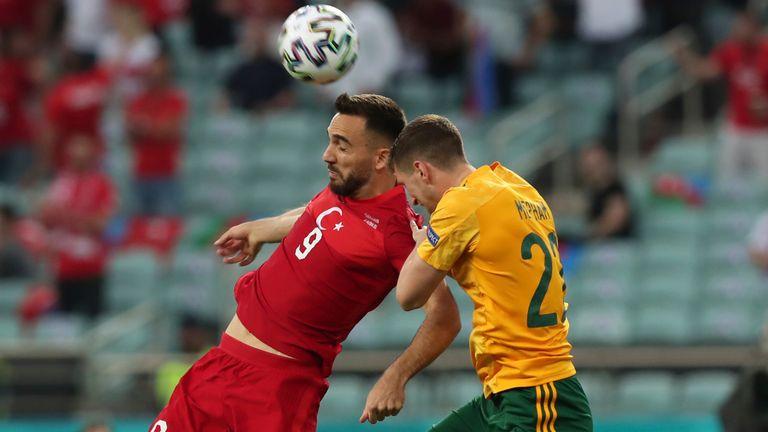 Turkey's Kenan Karaman jumps for the ball with Wales' Chris Mepham (AP)