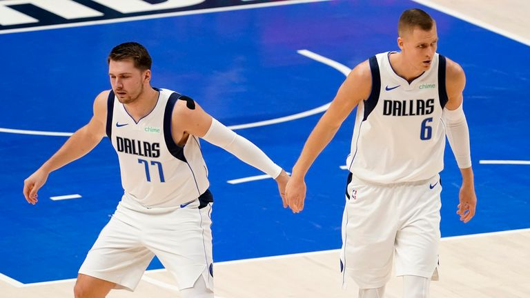 Dallas Mavericks' Luka Doncic and Kristaps Porzingis celebrate an early basket by Porzingis in the first half in Game 4 of an NBA basketball first-round playoff series against the Los Angeles Clippers