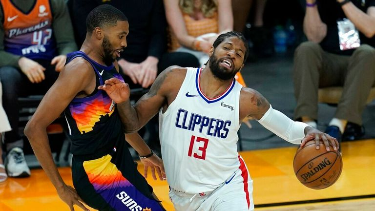 Los Angeles Clippers guard Paul George (13) collides with Phoenix Suns forward Mikal Bridges, left, during the second half of Game 1 of the NBA basketball Western Conference finals Sunday, June 20, 2021, in Phoenix. The Suns defeated the Clippers 120-114. (AP Photo/Ross D. Franklin)