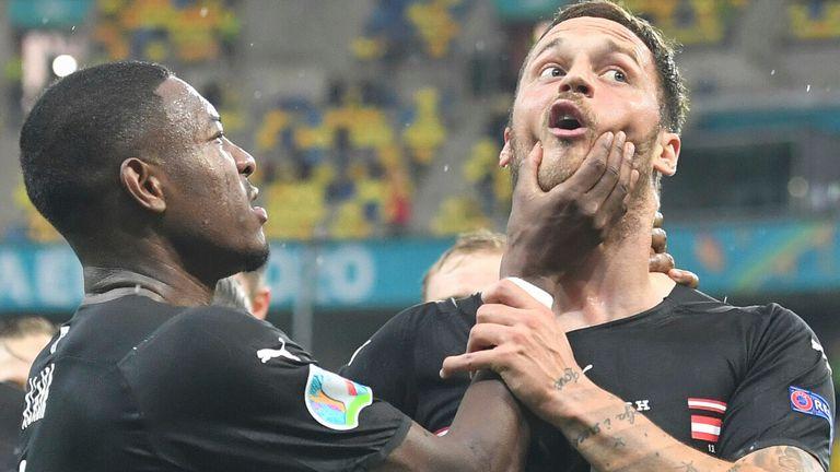 Austria captain David Alaba restrains Marko Arnautovic as the latter celebrates a goal against North Macedonia (AP)