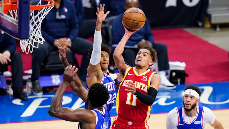 Trae Young attempts a floater over Matisse Thybulle and Joel Embiid