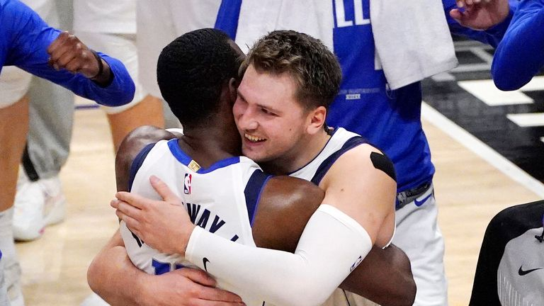 Dallas Mavericks guard Luka Doncic, center right, hugs forward Tim Hardaway Jr. after the Mavericks defeated the Los Angeles Clippers 105-100 in Game 5 of an NBA basketball first-round playoff series Wednesday, June 2, 2021, in Los Angeles.