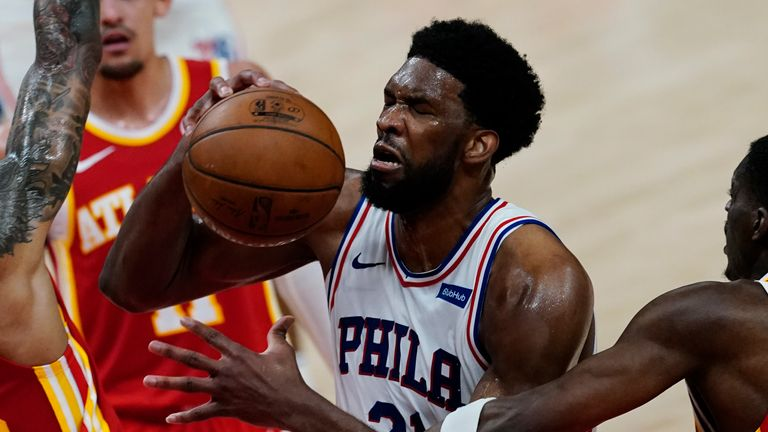 Philadelphia 76ers center Joel Embiid (21) is fouled by Atlanta Hawks forward Tony Snell (19), right, as Hawks forward John Collins (20) defends during the first half of Game 3 of a second-round NBA basketball playoff series, Friday, June 11, 2021, in Atlanta.