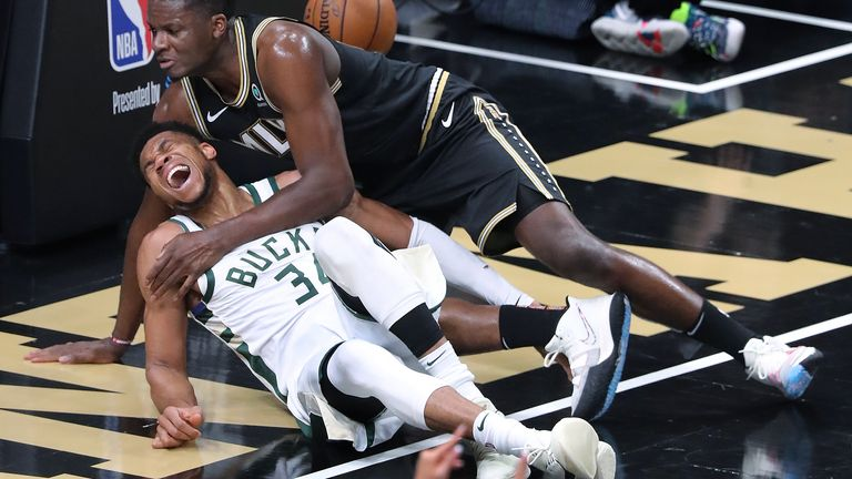 Atlanta Hawks center Clint Capela, top, and Milwaukee Bucks forward Giannis Antetokounmpo fall to the court during the third quarter in Game 4 of the Eastern Conference finals in the NBA basketball playoffs Tuesday, June 29, 2021, in Atlanta. Antetokounmpo left the game.