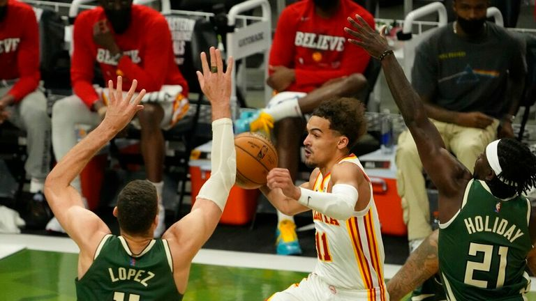 Atlanta Hawks' Trae Young drives between Milwaukee Bucks' Jrue Holiday and Brook Lopez during the first half of Game 1 of the NBA Eastern Conference basketball finals game Wednesday, June 23, 2021, in Milwaukee. (AP Photo/Morry Gash)