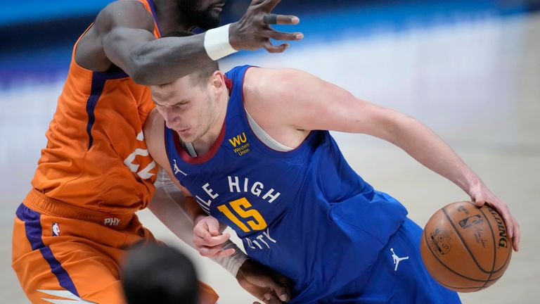 Denver Nuggets center Nikola Jokic drives as Phoenix Suns center Deandre Ayton defends during the second half of Game 3 of an NBA second-round playoff series Friday, June 11, 2021, in Denver. Phoenix won 116-102.
