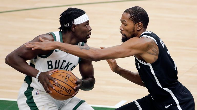 Milwaukee Bucks' Jrue Holiday drives to the basket against Brooklyn Nets' Kevin Durant