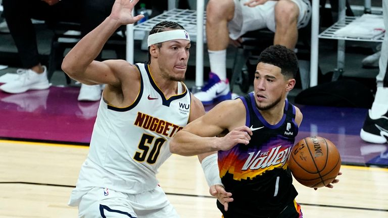 Phoenix Suns guard Devin Booker (1) drives as Denver Nuggets forward Aaron Gordon (50) defends during the second half of Game 1 of an NBA basketball second-round playoff series, Monday, June 7, 2021, in Phoenix.