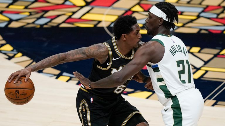 Atlanta Hawks' Lou Williams (6) keeps the ball away from Milwaukee Bucks' Jrue Holiday (21) during the first half of Game 4 of the NBA basketball Eastern Conference finals Tuesday, June 29, 2021, in Atlanta.