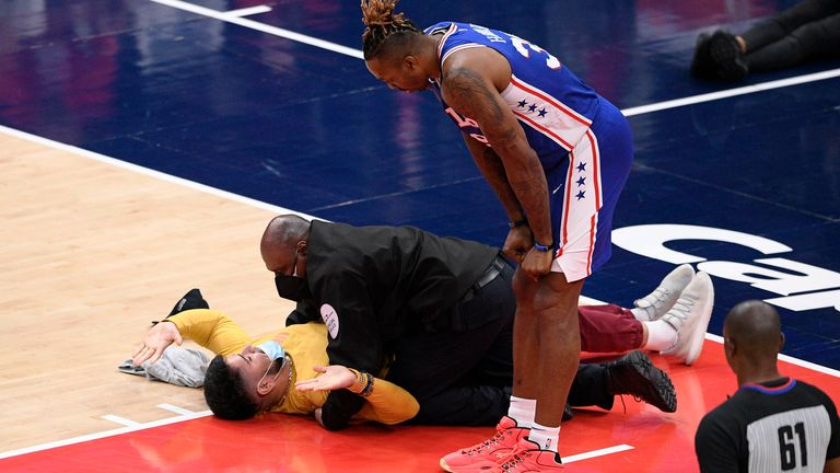 Philadelphia 76ers center Dwight Howard (39) watches as a fan who ran onto the court is restrained by security personnel during the second half of Game 4 in a first-round NBA basketball playoff series against the Washington Wizards, Monday, May 31, 2021, in Washington.