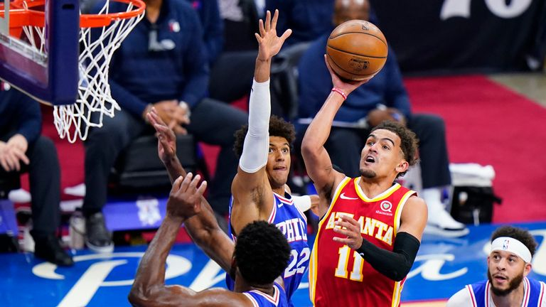 Atlanta Hawks' Trae Young (11) goes up for a shot against Philadelphia 76ers' Joel Embiid (21), Matisse Thybulle (22) and Seth Curry (31) during the second half of Game 5 in a second-round NBA basketball playoff series, Wednesday, June 16, 2021, in Philadelphia.