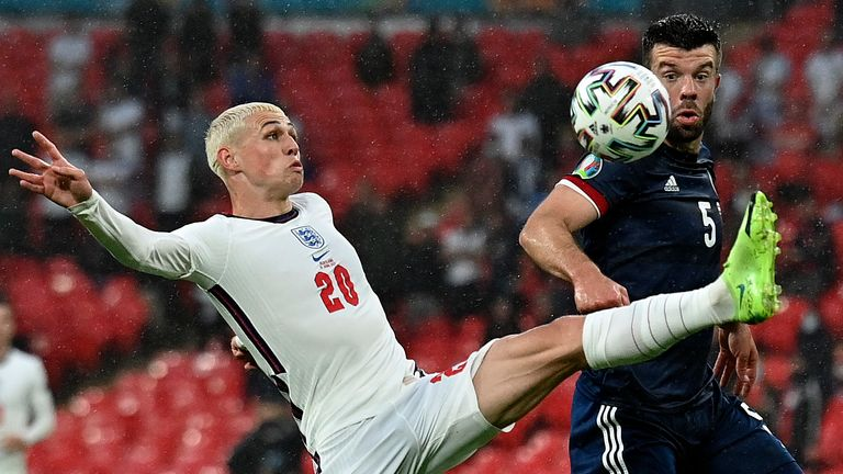 Phil Foden tries to control the ball under pressure from Grant Hanley during England vs Scotland