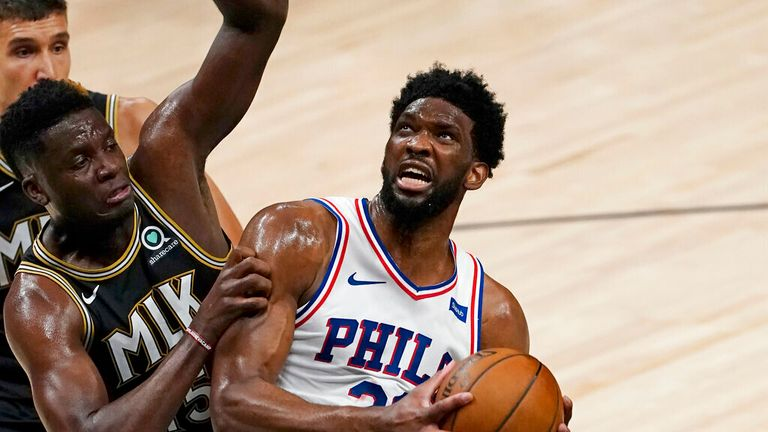 Philadelphia 76ers center Joel Embiid (21) is defended by Atlanta Hawks center Clint Capela (15) as he goes in for a basket during the first half of Game 6 of an NBA basketball Eastern Conference semifinal series Friday, June 18, 2021, in Atlanta. (AP Photo/John Bazemore)