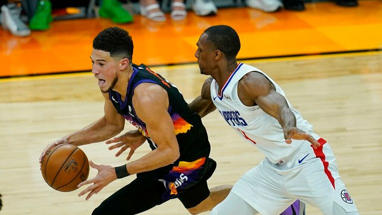 Phoenix Suns guard Devin Booker, left, drives past Los Angeles Clippers guard Rajon Rondo during the first half of Game 1 of the NBA basketball Western Conference finals Sunday, June 20, 2021, in Phoenix. The Suns defeated the Clippers 120-114. (AP Photo/Ross D. Franklin)