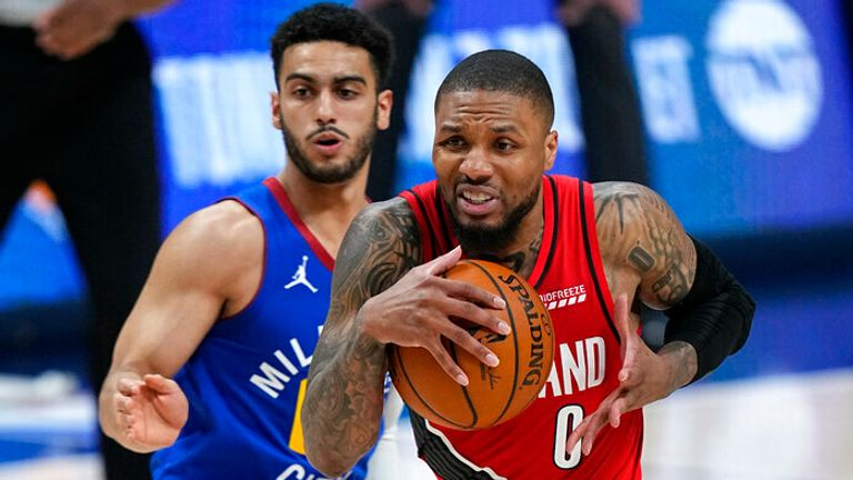 Portland Trail Blazers guard Damian Lillard (0) drives to the basket against Denver Nuggets guard Markus Howard during the second half of Game 5 of a first-round NBA basketball playoff series Tuesday, June 1, 2021, in Denver. (AP Photo/Jack Dempsey)