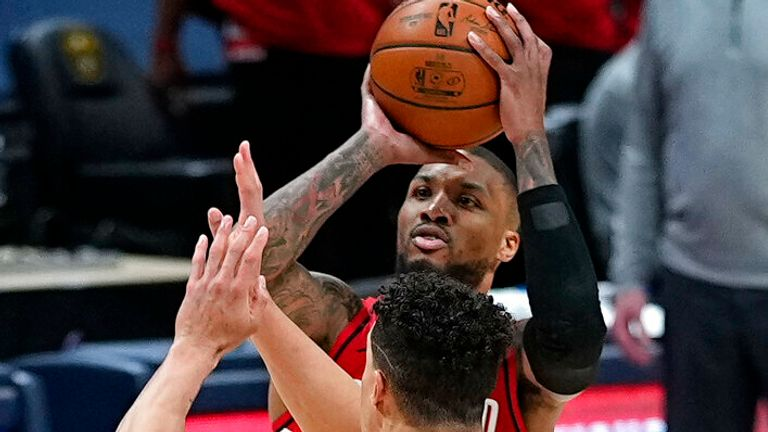 Portland Trail Blazers guard Damian Lillard (0) shoots a 3-point basket at the buzzer against Denver Nuggets forward Michael Porter Jr. (1) to send Game 5 of a first-round NBA basketball playoff series into overtime Tuesday, June 1, 2021, in Denver. (AP Photo/Jack Dempsey)