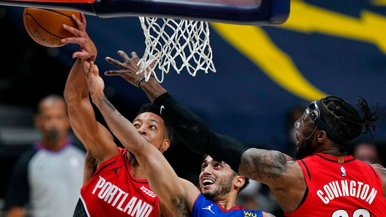 Portland Trail Blazers guard CJ McCollum (3) knocks the ball from the hand of Denver Nuggets guard Markus Howard (00) as Trail Blazers forward Robert Covington (23) defends during the first half of Game 5 of a first-round NBA basketball playoff series Tuesday, June 1, 2021, in Denver. (AP Photo/Jack Dempsey)