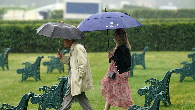 Two racegoers brave the wet conditions to get a trackside view on Friday at Royal Ascot