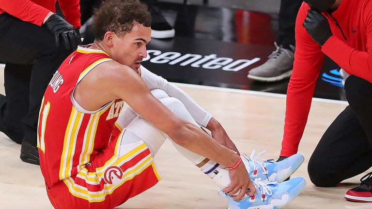 Atlanta Hawks guard Trae Young grabs his ankle after falling to the hardwood against the Milwaukee Bucks during Game 3