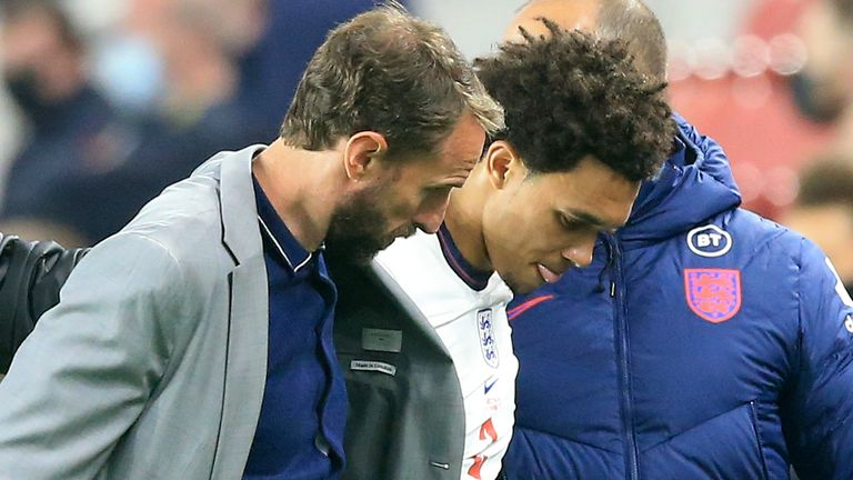 England coach Gareth Southgate assists England's Trent Alexander-Arnold after he came off the pitch injured during the friendly match with Austria.