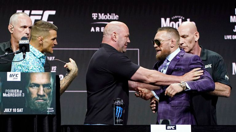 Dana White, center, UFC President, holds Conor McGregor away from Dustin Poirier during a news conference for a UFC 264 mixed martial arts bout Thursday, July 8, 2021, in Las Vegas. (AP Photo/John Locher)