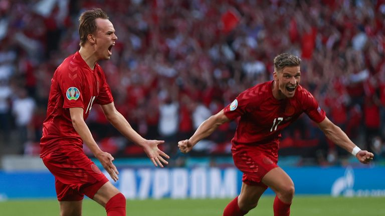 Denmark's Mikkel Damsgaard, left, celebrates with Jens Stryger Larsen after scoring his side's opening goal during the Euro 2020 soccer championship semifinal match between England and Denmark at Wembley